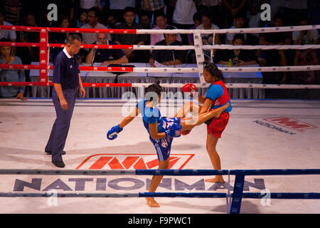 Female muay thai kickboxer in blue kick jab kicking oppenent is blocked by the arm as male referee officiates at - Stock Photo
