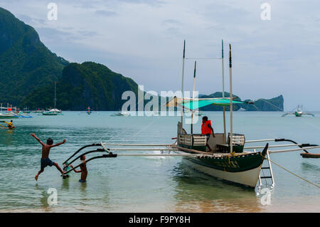 Children Playing By The Boat in the Seashore - Stock Photo