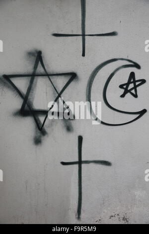 Religious symbols tagged on a wall. - Stock Photo