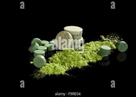 Green dietary supplements. Pills, ground powder, effervescent pills of chlorella, spirulina, wheat grass and barley - Stock Photo