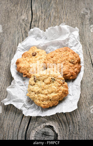 Oats cookies on baking paper over wooden background - Stock Photo