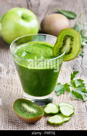 Green smoothie with kiwi, cucumber, apple on rustic table - Stock Photo