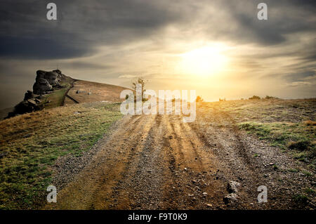 Stony road in mountains at the sunset - Stock Photo