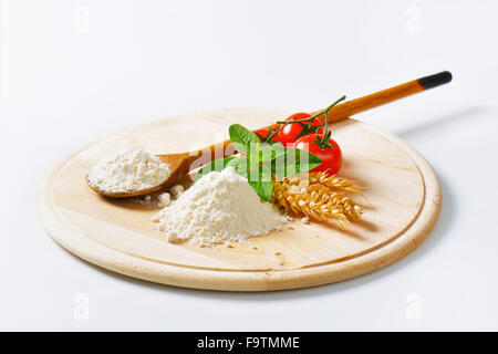 soft wheat background pile of soft wheat flour wooden spoon and fresh tomatoes on round