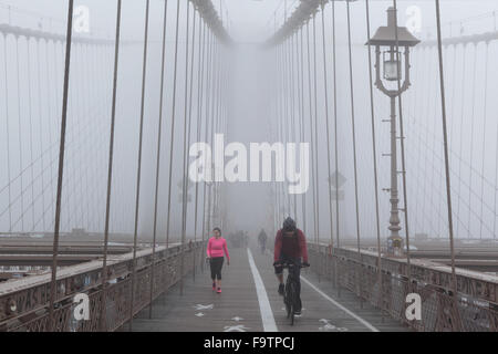 Brooklyn Bridge in fog with cyclists on the walkway - Stock Photo