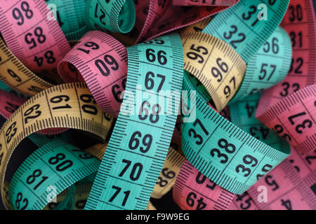 Colorful measuring tapes pile. Close up. - Stock Photo
