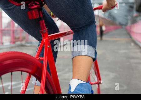 Legs of woman on red bicycle, close-up - Stock Photo