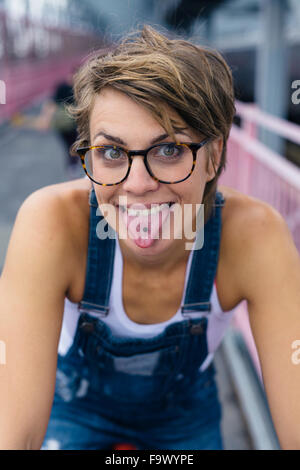 Portrait of woman showing her pierced tongue - Stock Photo