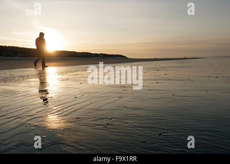 Germany, Langeoog Island, man walking on the beach at sunset - Stock Photo