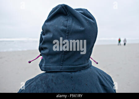 Germany, Langeoog Island, person with wet hood on the beach - Stock Photo