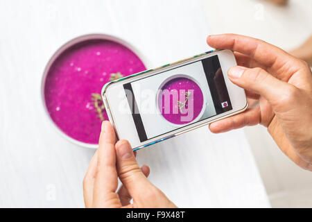 Woman taking a photo of dragon fruit smoothie with her smartphone, close-up - Stock Photo
