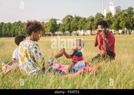 Family of four resting with blanket in a field - Stock Photo