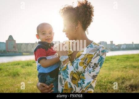 Germany, Cologne, mother holding son at River Rhine - Stock Photo
