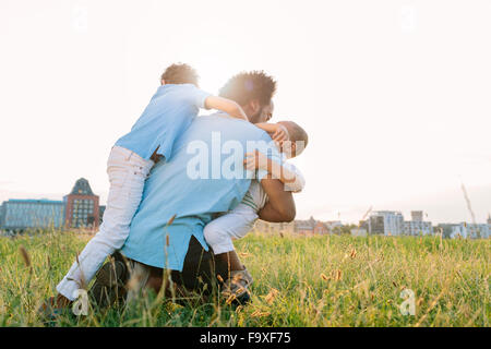 Germany, Cologne, playful father with two sons in field - Stock Photo