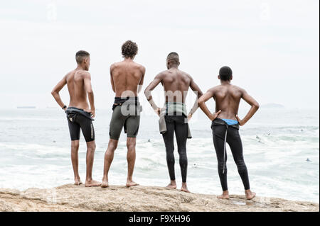 RIO DE JANEIRO, BRAZIL - OCTOBER 22, 2015: Brazilian surfers in wetsuits look at incoming waves at Praia do Diabo - Stock Photo