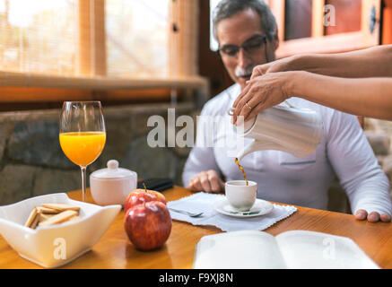 Man sitting at breakfast while woman pouring coffee into his cup - Stock Photo