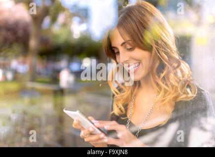 Portrait of happy young woman looking at her smartphone - Stock Photo