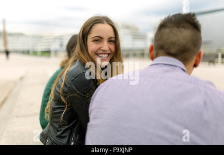 Portrait of happy teenage girl with friends outdoors - Stock Photo