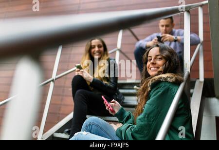 Three friends hanging around with cell phones oudoors - Stock Photo