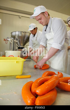 Butchers at the sausage machine making pork sausages. - Stock Photo