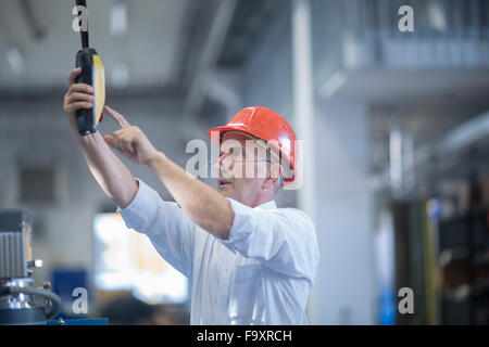 Man with red safety helmet operating lifting system - Stock Photo