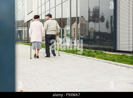 Senior couple walking with walking sticks on pavement - Stock Photo