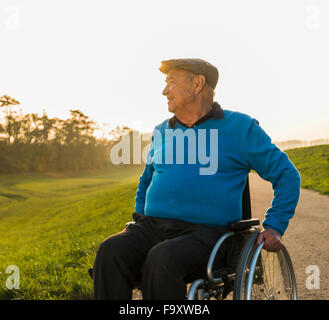 Senior man in wheelchair in the nature - Stock Photo