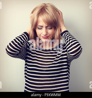 Depressed young blond woman with headache holding head the hands with unhappy face. Toned portrait - Stock Photo
