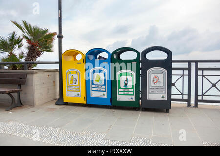 Four colour-coded recycling bins on a beach promenade in Italy (Monterosso Al Mare, Italy) - Stock Photo