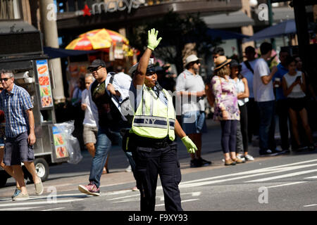 Police woman directing traffic near Herald Square in midtown Manhattan, New York City, USA - Stock Photo
