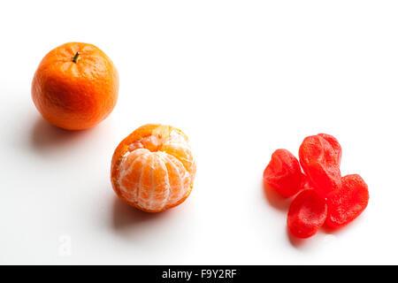 Peeled tangerine or mandarin fruit and candied orange fruit isolated on white background cutout