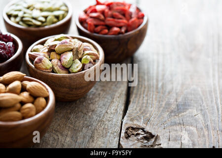 Variety of nuts and dried fruits in small wooden bowls - Stock Photo