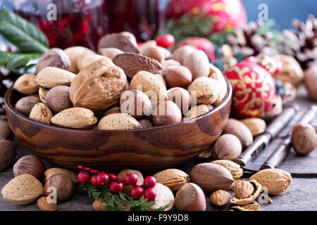 Variety of nuts with shells in a brown bowl - Stock Photo