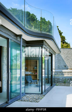 Exterior of a modern house from the patio, looking in to the main living space. Large sliding glass doors open. - Stock Photo