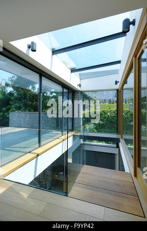 Glazed atrium and staircase in residential house uk stock for Floor to ceiling glass panels