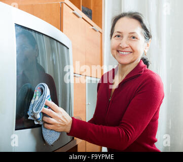 Happy mature woman dusting TV - Stock Photo