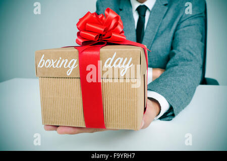 a young caucasian man in suit sitting at his office holding a gift tied with a red ribbon and the text boxing day - Stock Photo
