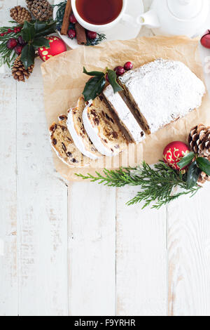 Christmas stollen with dried fruits and marzipan served with tea and decorations - Stock Photo
