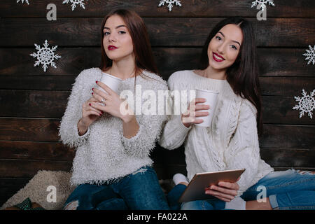 Two girls watching something on a tablet - Stock Photo