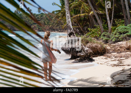 Beautiful Blond Woman with pink bag walking barefoot along the lonely caribbean white sand beach and coconut palm - Stock Photo