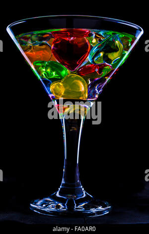 photo of a glass of the martini decorated with multi-colored hearts - Stock Photo