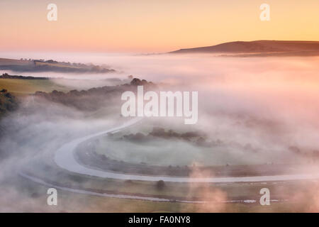 Mist floating over the river valley below with warm morning sunlight - Stock Photo