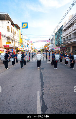 Group of high school teenagers playing music in a marching band at the annual Surin Elephant Roundup parade in downtown - Stock Photo