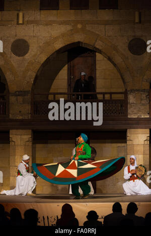 A Sufi dancer in green spinning his dress during a whirling dervish performance, a famous tourist attraction, at - Stock Photo