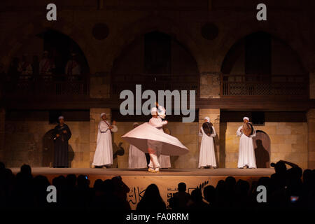 A Sufi dancer in white dress twirling around in a whirling dervish at an open air courtyard performance at the Al - Stock Photo
