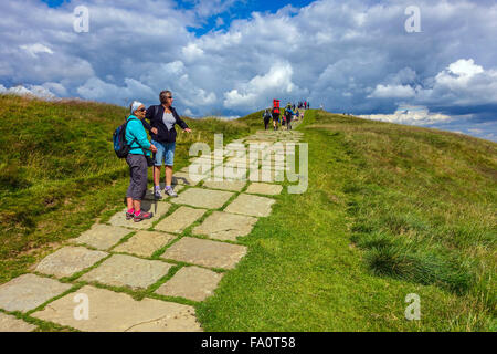 Hikers on the flagged footpath on Mam Tor the Great Ridge above Castleton, Peak District Derbyshire - Stock Photo