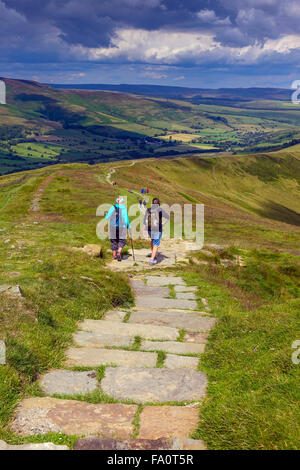 Hikers on the flagged footpath along the Great Ridge above Castleton, Peak District Derbyshire - Stock Photo