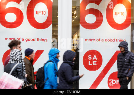 Bath, UK, 19th December, 2015. Shoppers in Bath city centre are pictured passing in front of a shop window displaying - Stock Photo
