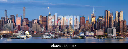 Midtown West Manhattan skyscrapers & the Hudson River. Panoramic view in early evening with moonrise and New York - Stock Photo