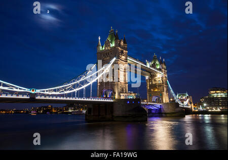 A dusk-time view of the magnificent Tower Bridge spanning over the River Thames in London. - Stock Photo